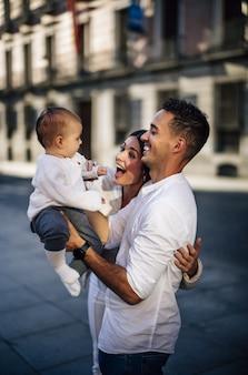 Вертикальный снимок счастливой кавказской семьи с маленьким ребенком на руках