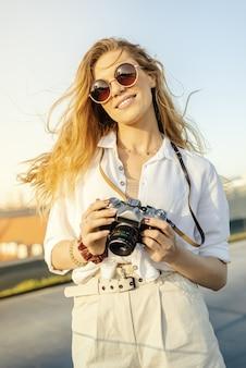 Вертикальный снимок счастливой, модно одетой путешественницы с фотоаппаратом в солнечную погоду