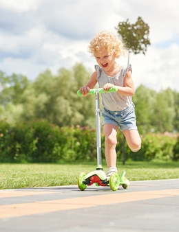 Вертикальный снимок счастливой маленькой девочки, радостно смеющейся во время езды на самокате в парке в теплый солнечный день, концепция счастья для детей.
