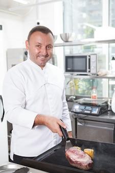 Вертикальный снимок счастливого шеф-повара ресторана, улыбающегося во время работы на кухне