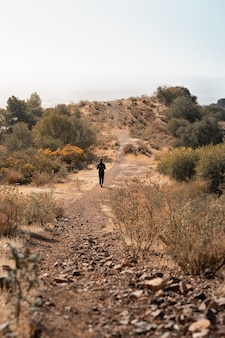 Вертикальный снимок туриста, поднимающегося на холм в окружении деревьев и кустов