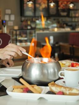 레스토랑 테이블에 화염이 있는 뜨거운 수프의 세로 샷