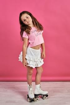 분홍색 벽 앞에서 롤러 스케이트를 입고 포즈를 취하는 어린 소녀의 세로 샷