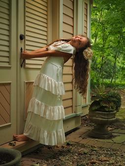 Вертикальный снимок маленькой девочки с длинными волосами в белом платье, закрывающей дверь дома