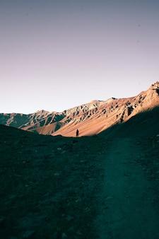 일몰 동안 산에서 걷는 외로운 사람의 세로 샷