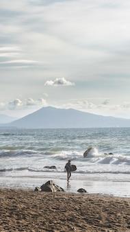 바다에 외로운 서퍼의 세로 샷