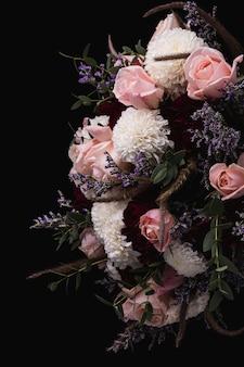 黒の背景にピンクと赤のバラと白いダリアの豪華な花束の垂直ショット