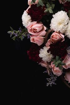 Вертикальный снимок роскошного букета из розовых роз и белых, красных георгинов на черном фоне
