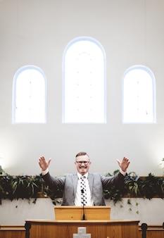 Вертикальный снимок мужчины в костюме, проповедующего слова библии у алтаря церкви