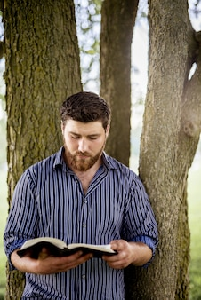 남자의 세로 샷은 성경을 읽는 동안 나무에 기댈