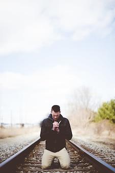 Вертикальный снимок мужчины, стоящего на коленях на железнодорожных путях и молящегося с закрытыми глазами.