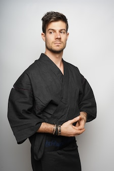 Вертикальный снимок мужчины, стоящего в кимоно в японском стиле.