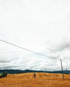 Вертикальный снимок мужчины, стоящего в пустом поле под облачным небом