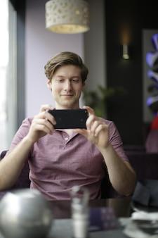 彼の携帯電話で写真を撮る男性の垂直ショット