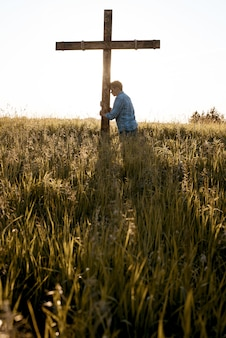 芝生のフィールドで木製の十字架に対して彼の頭を持つ男性の垂直ショット
