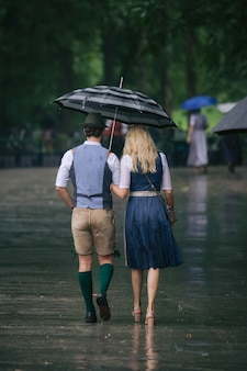 Вертикальный снимок мужчины и женщины, идущих рядом под зонтиком