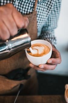 カフェでカプチーノカップに牛乳を注ぐ男の垂直ショット