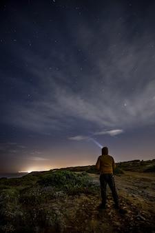 바위에 서서 밤에 빛나는 별을 보는 남자의 세로 샷