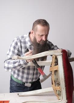 Вертикальный снимок мужчины с длинной бородой и усами, ремонтирующего сломанный стул
