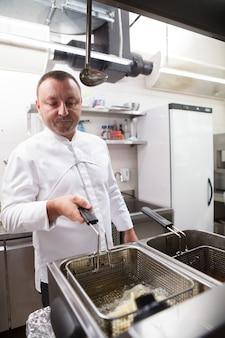 Вертикальный снимок зрелого шеф-повара, жарящего картофель фри на кухне своего ресторана
