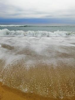 산 세바스티안 리조트 타운, 스페인의 해변 위에 매혹적인 일몰의 세로 샷