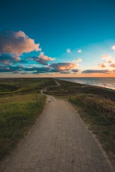 オランダ、ドンブルグで撮影された曇り空の下の海沿いの舗装された小道の垂直ショット