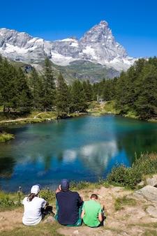 遠くに山のある木々に囲まれた池の近くに座っている人の垂直方向のショット