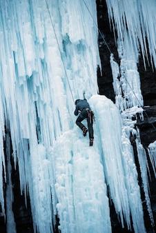 氷に覆われた岩の崖を登る人の垂直ショット