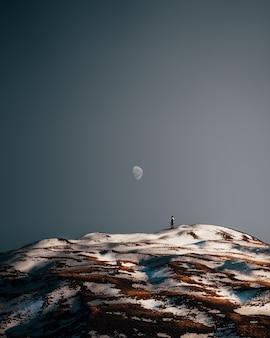 경치 좋은 눈 덮인 언덕에서 혼자 하이킹하는 사람의 세로 샷