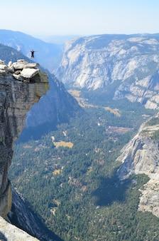 カリフォルニア州ヨセミテのハーフドームで崖の上をジャンプする人の垂直ショット