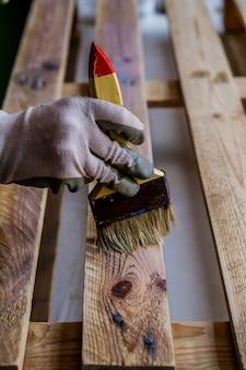 브러시로 나무 팔레트를 칠하는 사람의 세로 샷