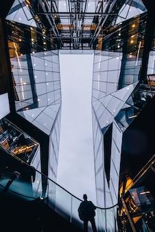 Вертикальный снимок человека, стоящего между небоскребами
