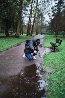 公園で水たまりのショットを撮る人の垂直ショット