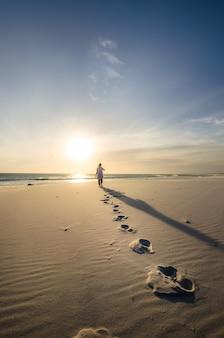 전경에 발자취와 모래 해변을 걷는 사람의 세로 샷