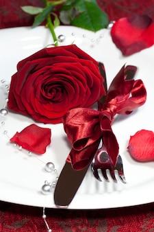 축제 테이블에 빨간 장미와 함께 접시의 세로 샷