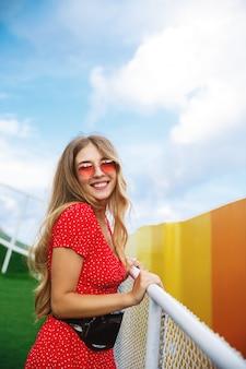 Вертикальный снимок довольно белокурой девушки в летнем платье и красных солнцезащитных очках, опирающейся на перила в парке.