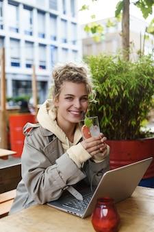 Вертикальный снимок довольно улыбающейся женщины, выглядящей счастливой, попивая коктейль, сидя в кафе на открытом воздухе, используя ноутбук.