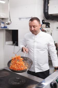 Вертикальный снимок профессионального шеф-повара, жарящего овощи