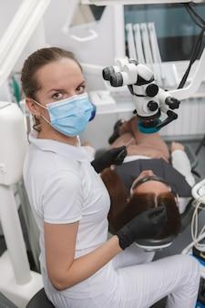 Вертикальный снимок профессионального стоматолога в медицинской маске, смотрящего вперед во время работы
