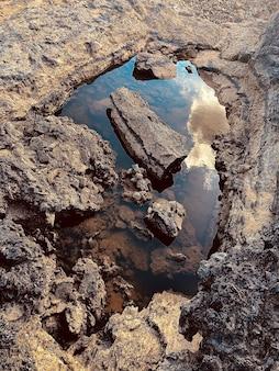 曇り空を反映した岩場の水たまりの垂直ショット