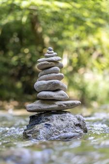강물에 균형 잡힌 돌 피라미드의 수직 샷