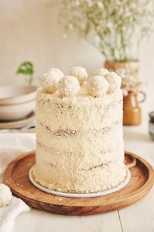 Вертикальный снимок торта рафаэлло на деревянном подносе с белой скатертью под ним