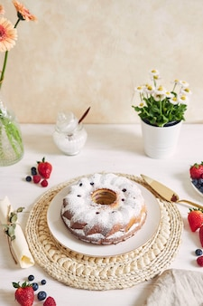 흰색 배경에 흰색 테이블에 과일과 가루와 반지 케이크의 세로 샷