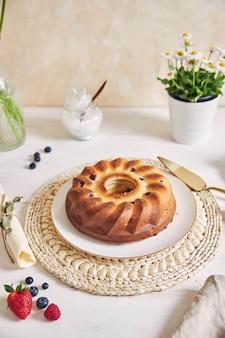 흰색 표면에 흰색 테이블에 과일과 함께 링 케이크의 세로 샷