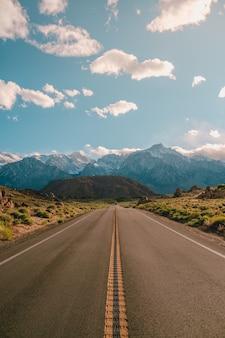 캘리포니아에서 포착된 푸른 하늘 아래 장엄한 산들이 있는 도로의 세로 샷
