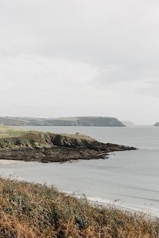 曇り空の下の海沿いの岩の崖の垂直ショット