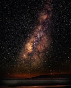 은하수와 별이 빛나는 하늘 아래 바다의 세로 샷