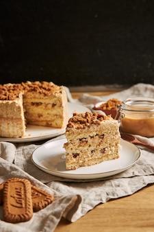 テーブルの上にクッキーとキャラメルとおいしいロータスクッキーケーキのスライスの垂直ショット