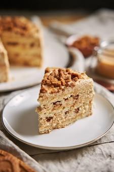 Вертикальный снимок кусочка вкусного торта с печеньем из лотоса с карамелью и печеньем на столе