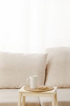 ライトの下でベージュのソファの近くにマグカップが置かれた小さなテーブルの垂直ショット